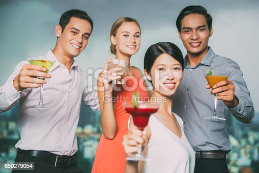 1165538246 istock photo Four Smiling People with Cocktails Toasting in Bar 650279054