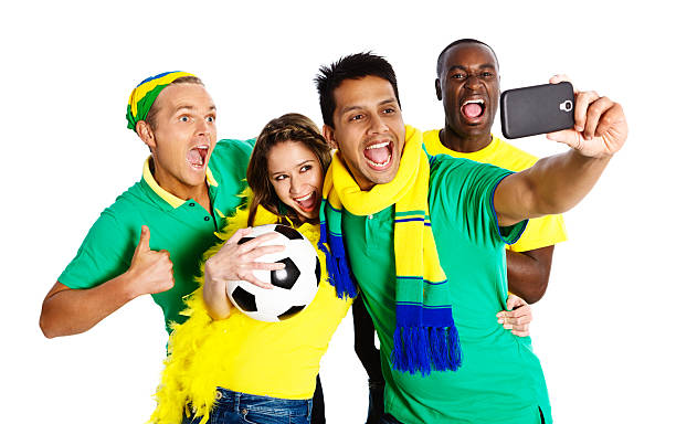 "Four soccer fans taking cell phone self portraits Four soccer fans in Brazilian team colors pull silly faces as they take ""selfies"" or cell phone self-portraits. fan club stock pictures, royalty-free photos & images"