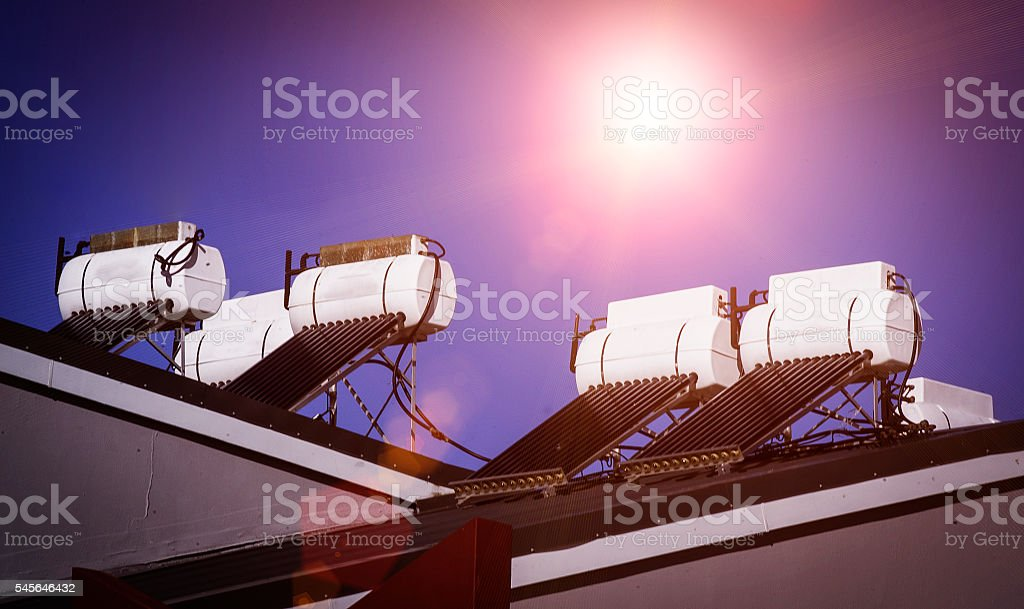 Four solar panels on a roof under the blazing sun stock photo
