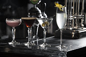 four special cocktails on a bar desk. black background.