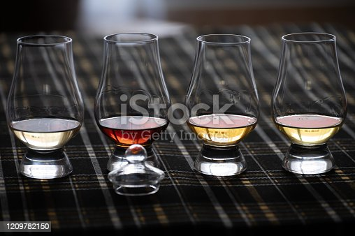istock Four Special tulip-shaped glasses for tasting of Scotch whisky on distillery in Scotland, UK and dark tartan 1209782150