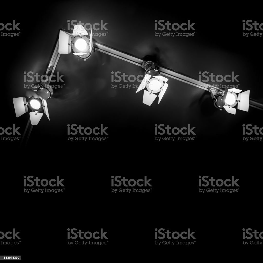 Four spot lights in metal body over black ceiling background, stage...