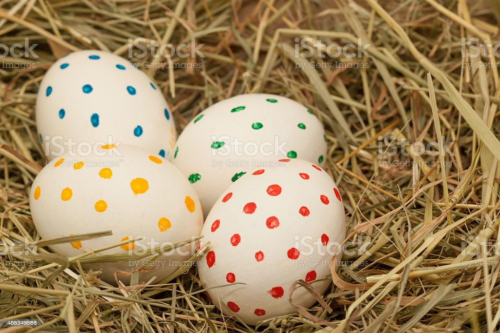four spotted easter eggs on hay royalty-free stock photo