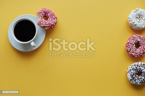istock Four sprinkled dontus and cup of coffee 636095858