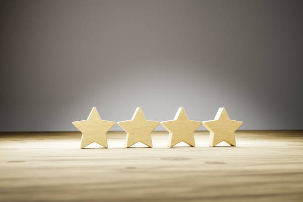 Four star rating: four wooden stars in a row on a wooden table with gray background. Selective focus. Concept shot for rating / reviews. stock photo