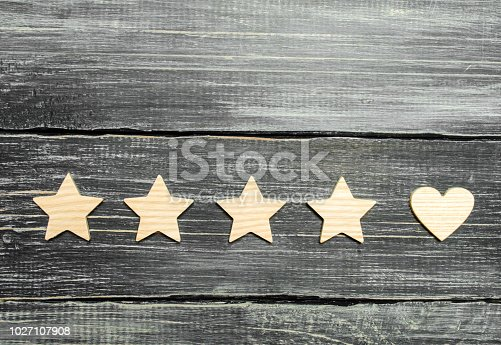 istock Four stars and a heart on a dark background. Selection of the user and clients. Universal recognition and admiration. Rating of a hotel or restaurant, commercial product or mobile application. 1027107908