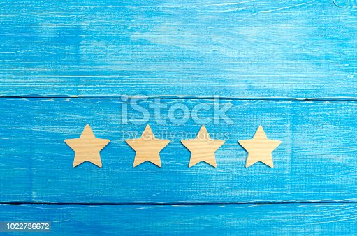 istock four stars on a blue background. The concept of rating and evaluation. The rating of the hotel, restaurant, mobile application. Quality service, buyer choice. Success in business 1022736672