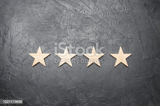 istock four stars on a dark background. The concept of rating and evaluation. The rating of the hotel, restaurant, mobile application. Quality service, buyer choice. Success in business 1007415658