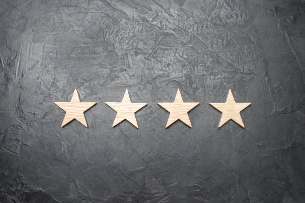 four stars on a dark background. The concept of rating and evaluation. The rating of the hotel, restaurant, mobile application. Quality service, buyer choice. Success in business stock photo