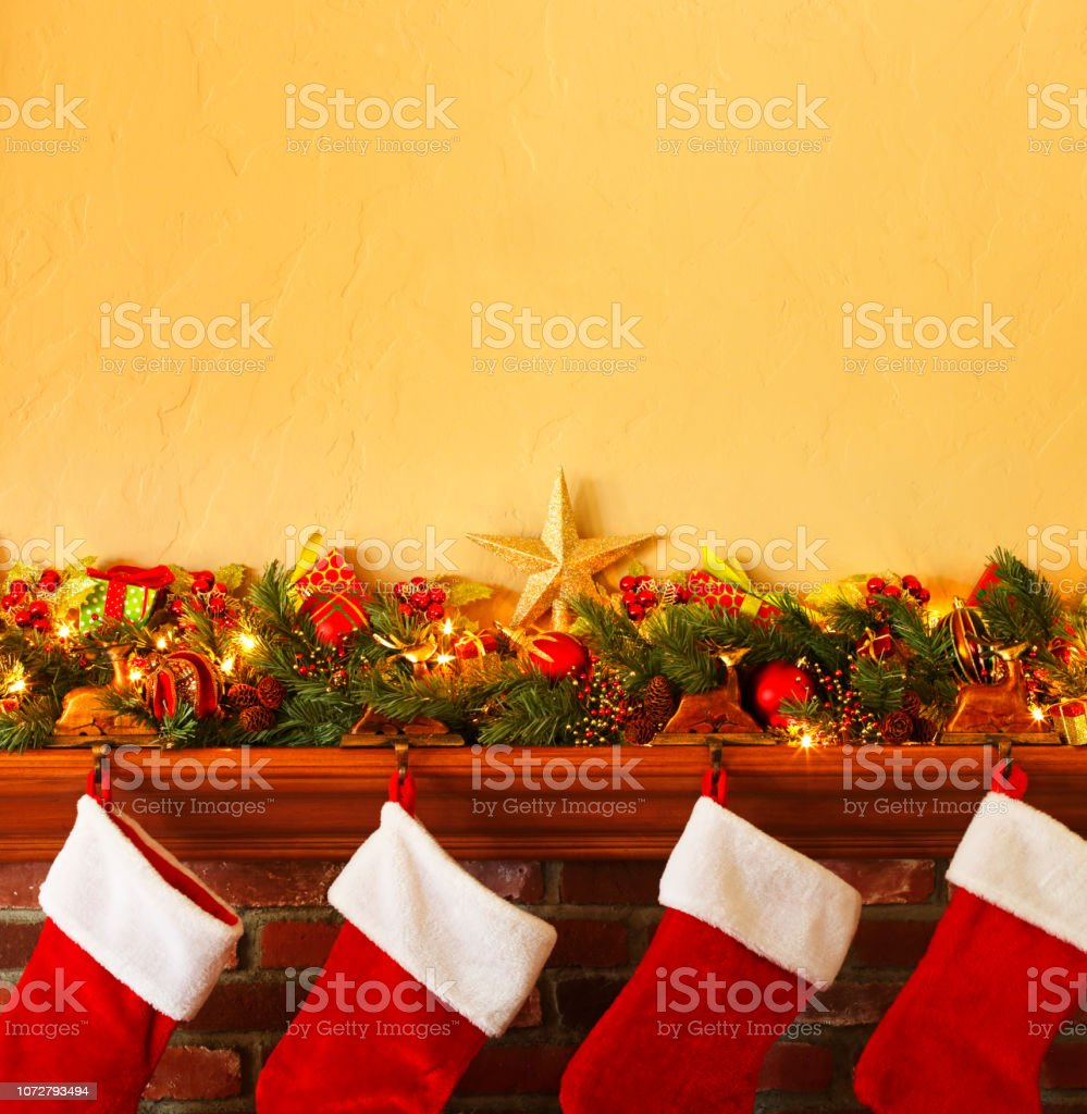 Four Stockings Hanging From A Christmas Mantelpiece stock photo