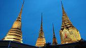 Four Stupa of Wat Pho shining in evening blue sky