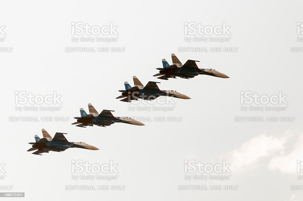 Four Su-27 form a rank against blue sky background royalty-free stock photo