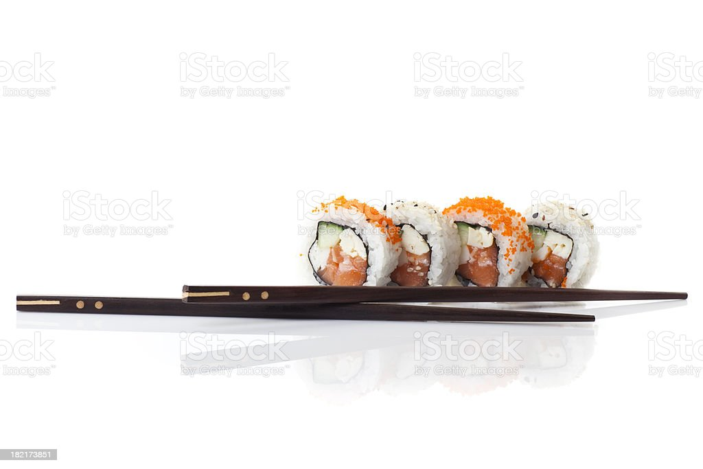 Four sushi rolls with two black chopsticks royalty-free stock photo