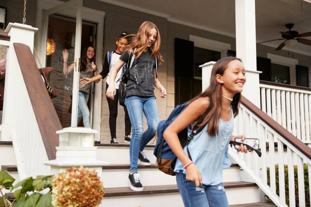 vier teenager-mädchen verlassen haus mit schultaschen - druck jeans stock-fotos und bilder