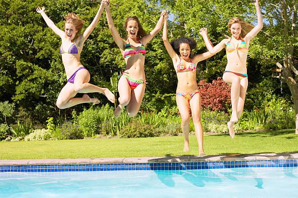 Four teenage girls jumping into pool stock photo