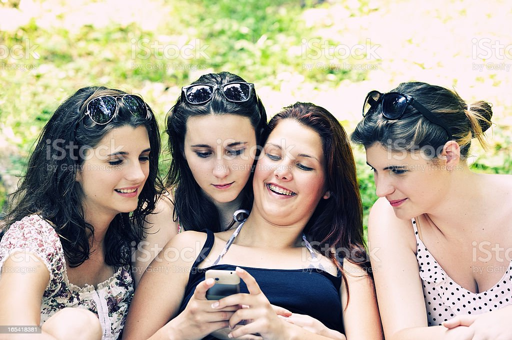 Four Teenage Girls Looking at Smartphone royalty-free stock photo