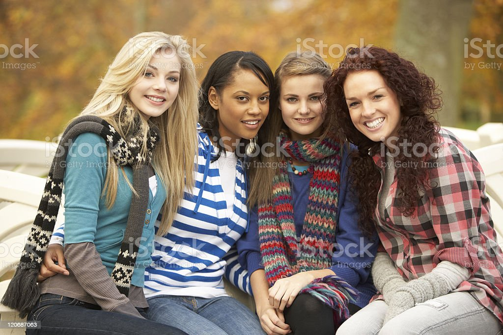 Four Teenage Girls Sitting On Bench In Autumn Park royalty-free stock photo