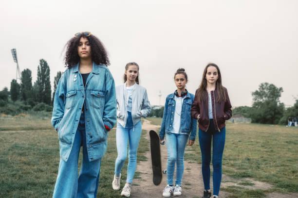 vier mädchen im teenageralter zu fuß im freien im park - stoffe berlin stock-fotos und bilder