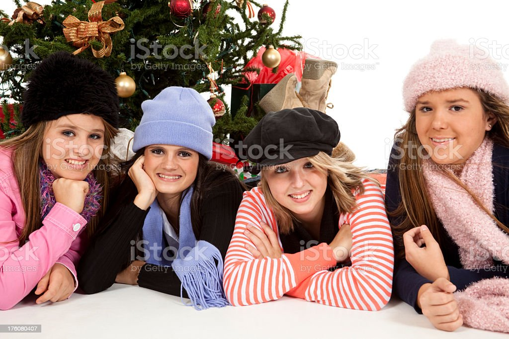 Four teenage girls wearing hats and scarfs by Christmas tree royalty-free stock photo