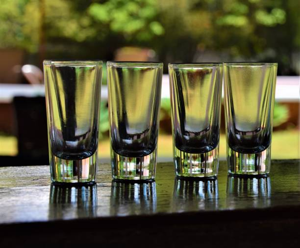 Four tequila whisky shot glasses on outside bar Four tequila whisky shot glasses on outside bar tequila shot stock pictures, royalty-free photos & images