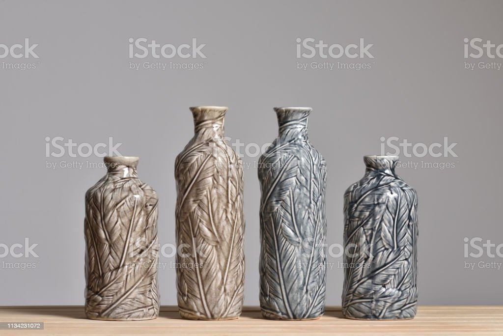 Four textured vases with leaf texture. Vases beige and gray on a...