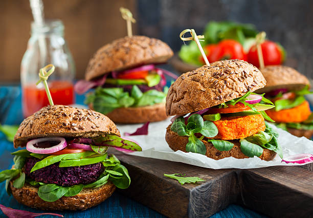 Four thick veggie beet, carrot and avocado burgers on rolls stock photo