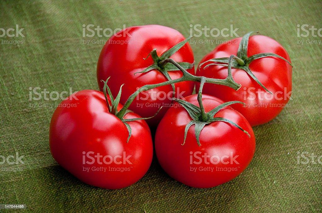 Four tomatoes  on a green napkin stock photo