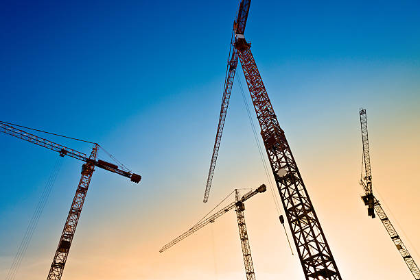 four tower cranes on the blue sky stock photo