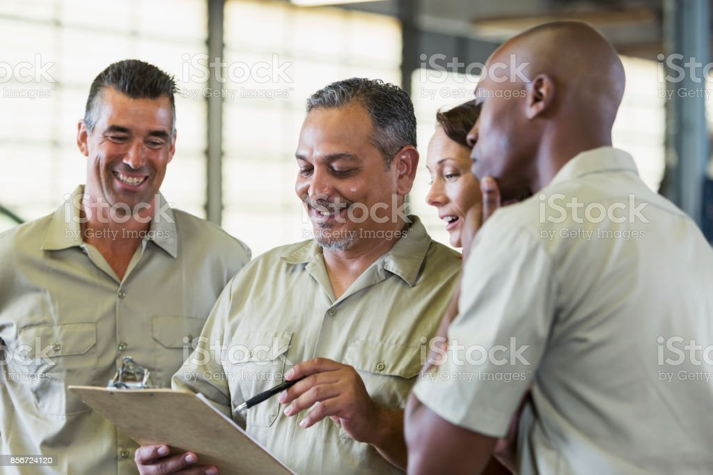 Four trucking company workers in garage stock photo