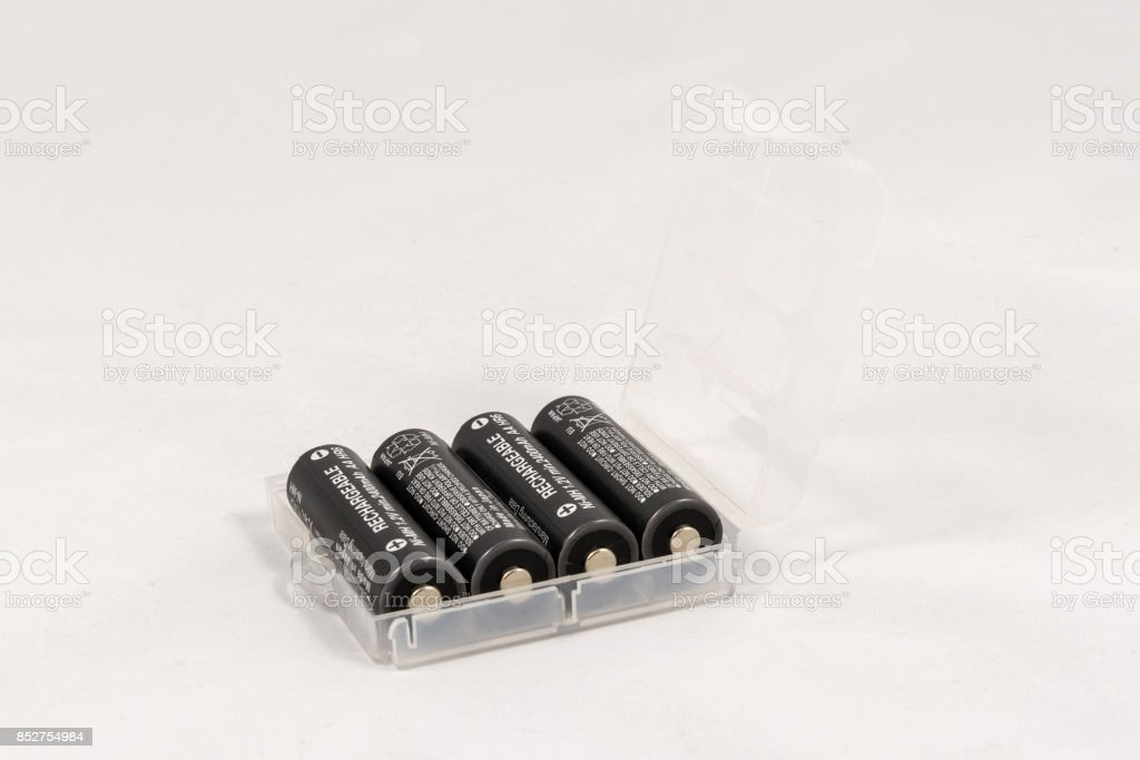 Four unbranded black AA rechargeable batteries in trasparent case stock photo