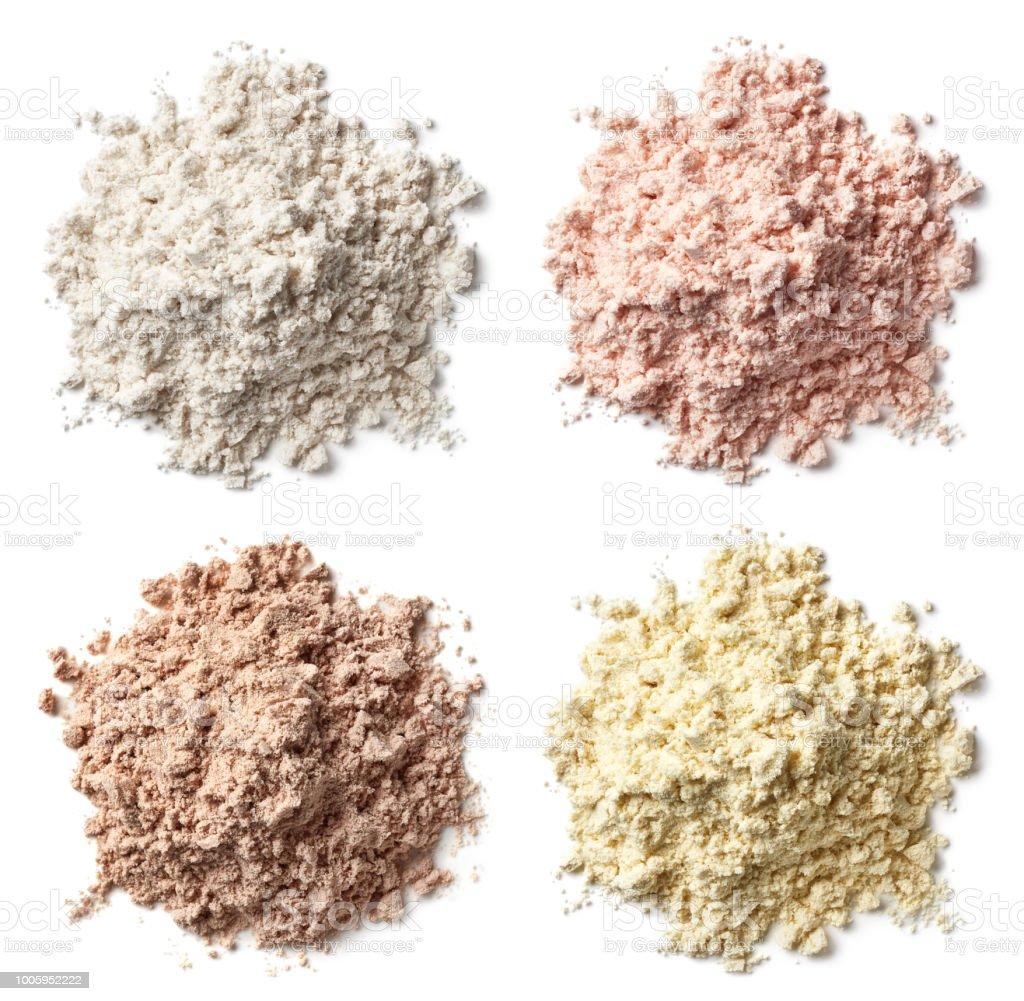 Four various heaps of protein powder (vanilla, strawberry, chocolate, banana) stock photo