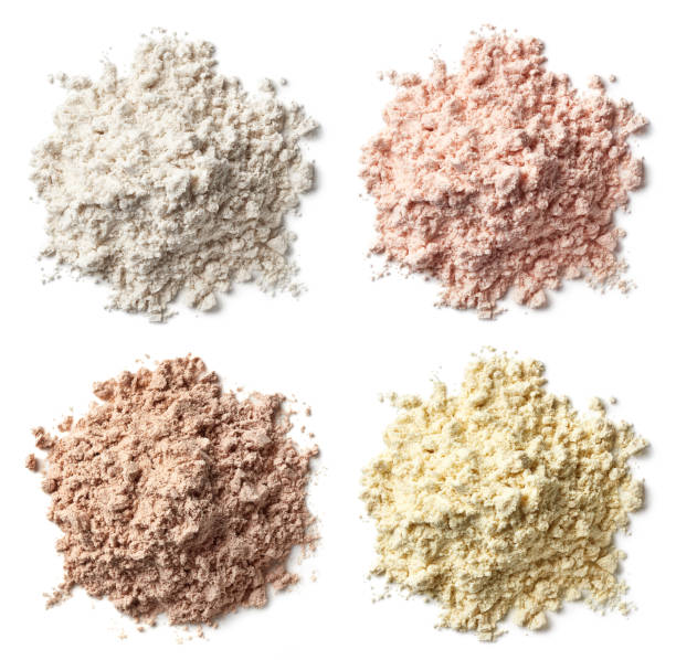 four various heaps of protein powder (vanilla, strawberry, chocolate, banana) - protein stock photos and pictures