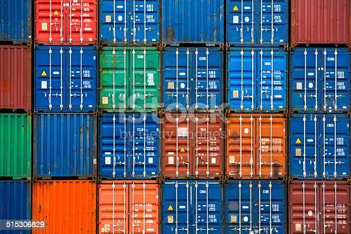 Four vertical rows of shipping containers that are different colors in the Port of Zeebrugge, Belgium
