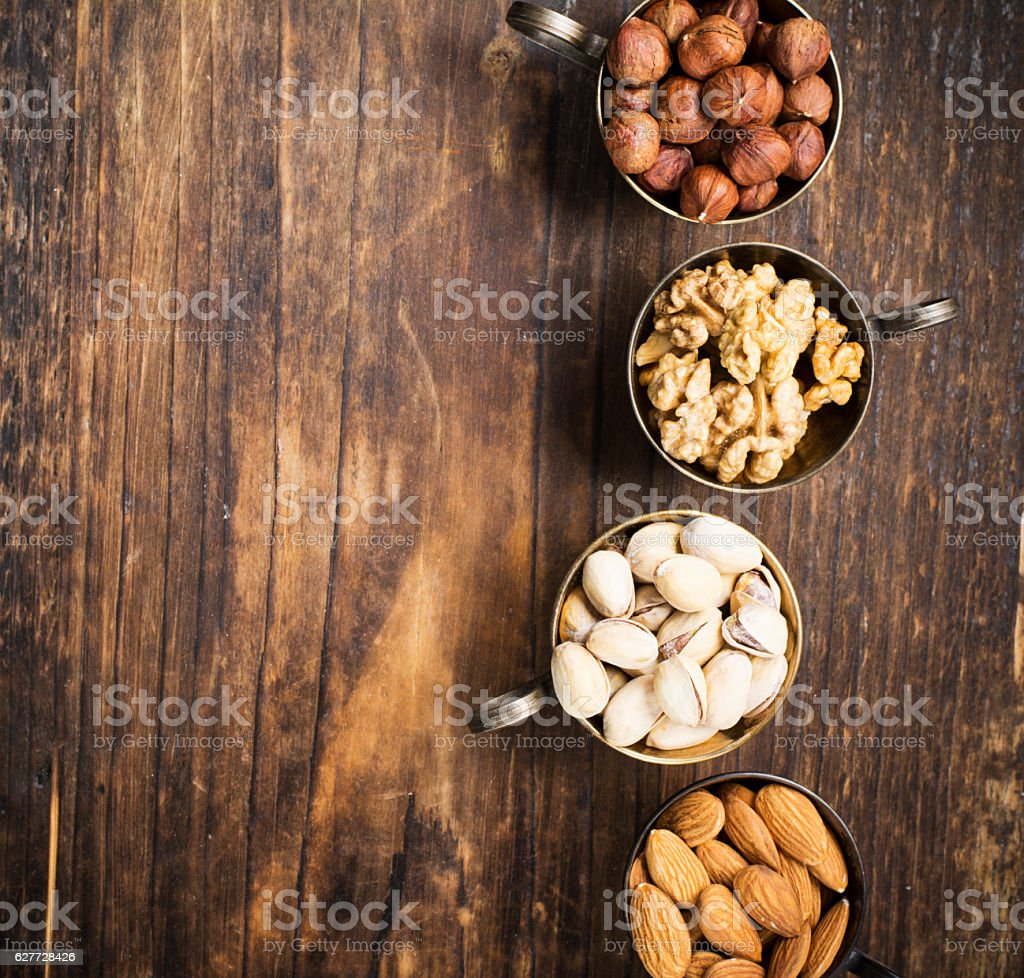 Four vintage cupro-nickel cup full of different nuts, almonds stock photo