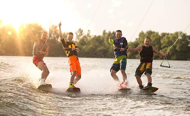 vier wake bord riders spaß - wassersport stock-fotos und bilder