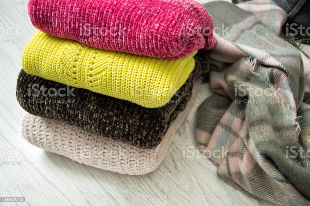 Four warm colour sweaters on a wooden background. Fashionable concept. stock photo