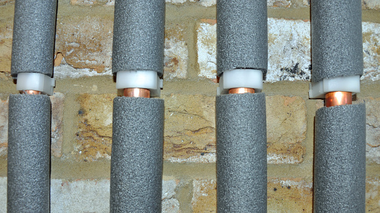 Four copper water pipes in grey foam insulation against an interior brick wall. Billericay, Essex, United Kingdom, March 25, 2020