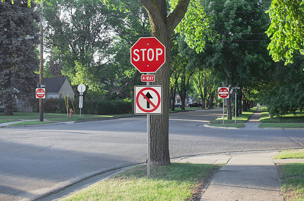 Four Way Stop Sign With One Way In American Suburb stock photo