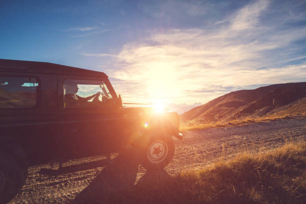 Quatre roues motrices sur la montagne au coucher du soleil avec - Photo