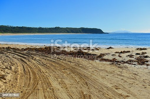 Curving four wheel drive tracks on a beach background