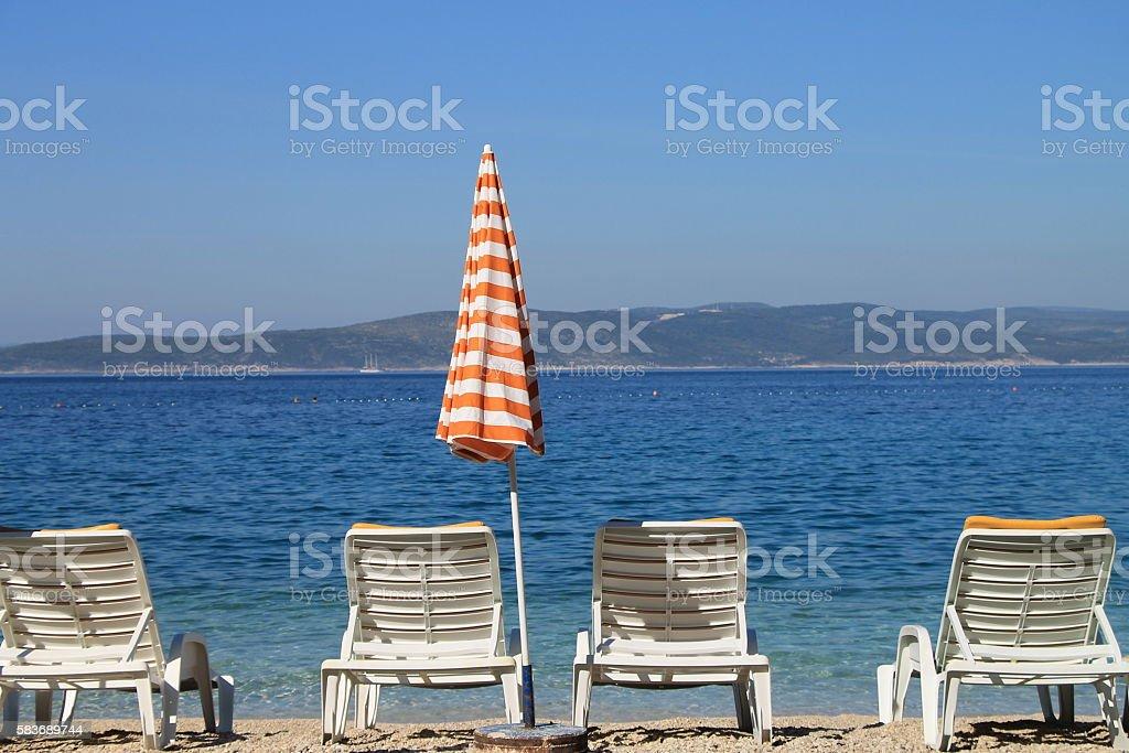 Four White Beach Chairs And Sun Umbrella In Brela Croatia Stock Photo Download Image Now Istock
