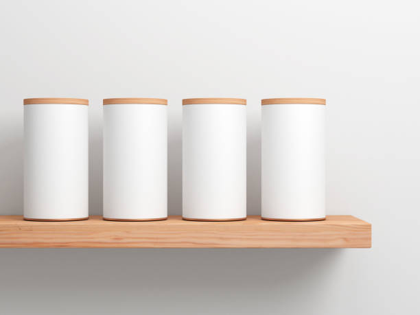 Four White Tin Can Mockup on wooden shelf. Cylindrical packaging stock photo