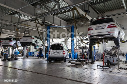 Novosibirsk, Russia - 08.01.2018: Four white used cars with an open hood raised on a lift for repairing the chassis and engine in a vehicle repair shop. Auto service industry.