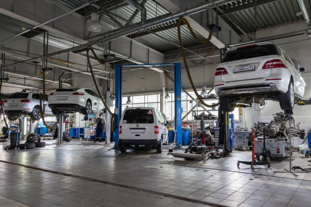 四輛白色二手車,在電梯上升起一個開放式引擎蓋,用於修理車輛修理店的底盤和發動機。汽車服務業。圖像檔