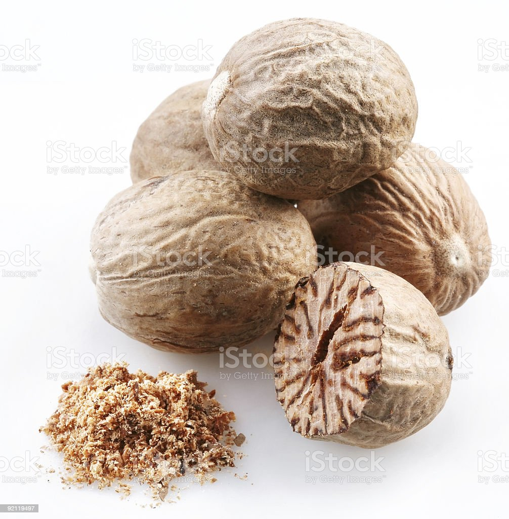 Four whole nutmegs, a half one and some ground nutmeg stock photo