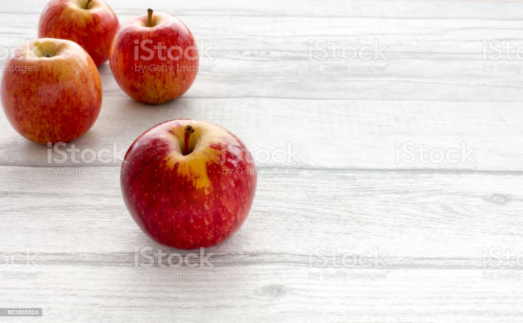 Four Whole Red Apples on Grey Wooden Background stock photo