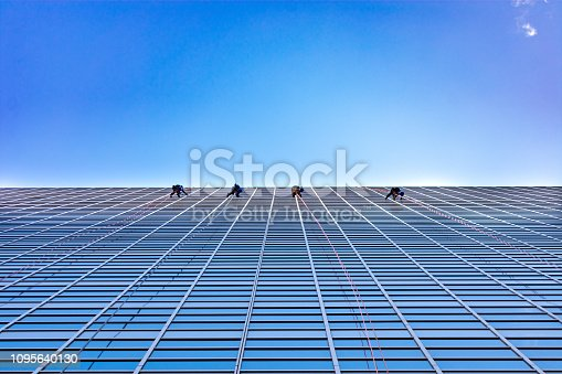 Four window washers cleaning on the side of a modern glass skyscraper in a city