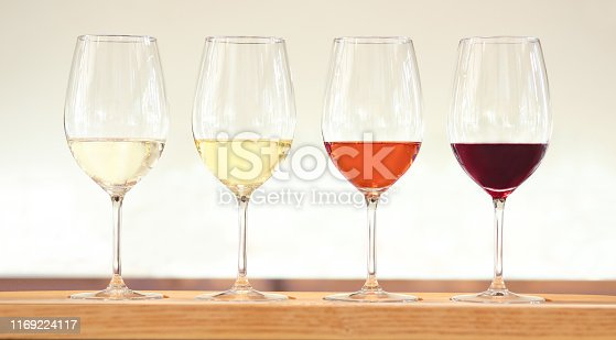 Four wine tasting glasses with white, red and rose wine