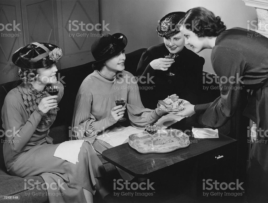 Four women drinking wine, talking in living room (B&W) stock photo