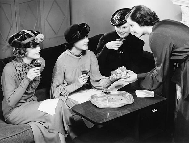 four women drinking wine, talking in living room (b&w) - 1930s style stock photos and pictures